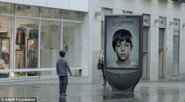 The poster is set to be installed across Spain - but when viewed from a child's perspective reveal a helpline number