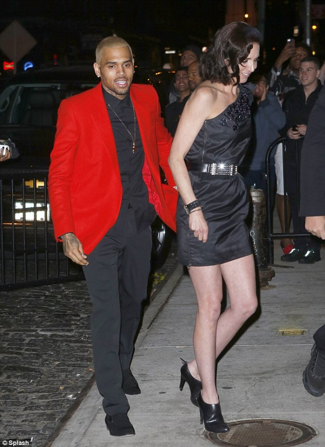 Red or dead: Chris Brown certainly stood out from the crowd in a bright red jacket as he made his way into the party