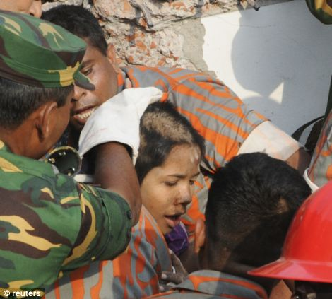 Rescue workers rescue a woman from the rubble of the Rana Plaza building 17 days after the building collapsed