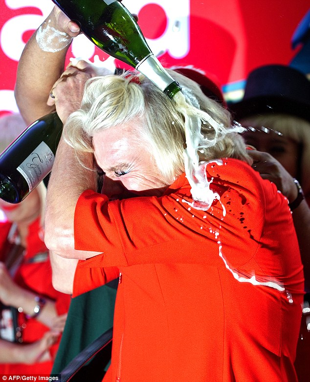 Celebrations: The billionaire was doused in champagne after finally completing his side of the bet