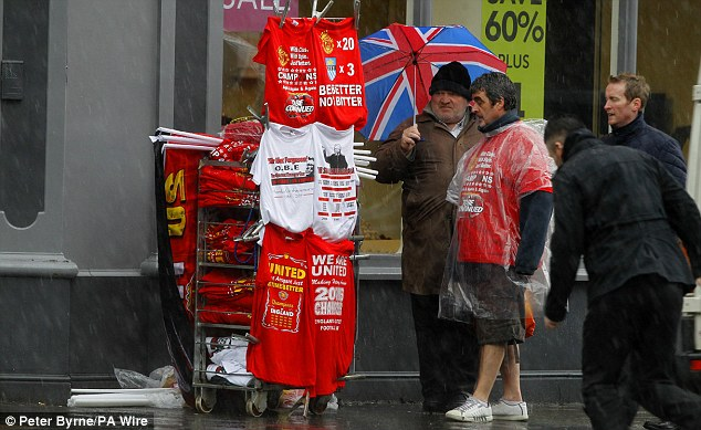 Cashing in: A stall holder sells Manchester United merchandise in the rain