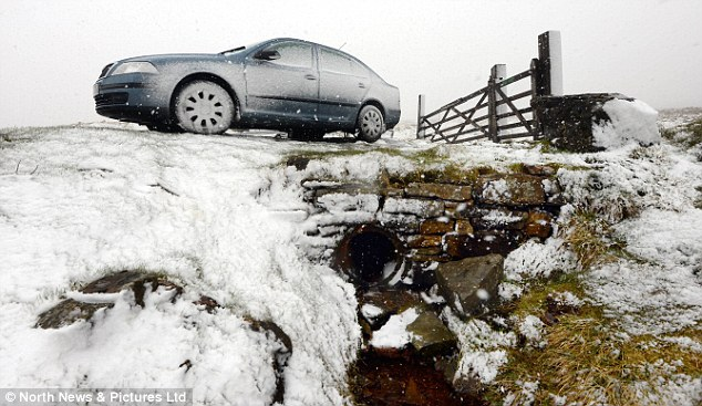 Slippery surfaces: A car is covered in a layer of snow after blizzards fell across the Pennines in Cumbria