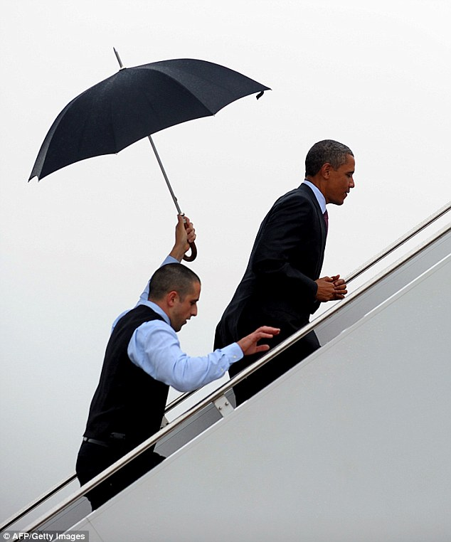 It doesn't rain it...Air Force One Staff Sergeant Brian Barnett is pictured following behind the President with an umbrella as he boards Air Force One in 2011
