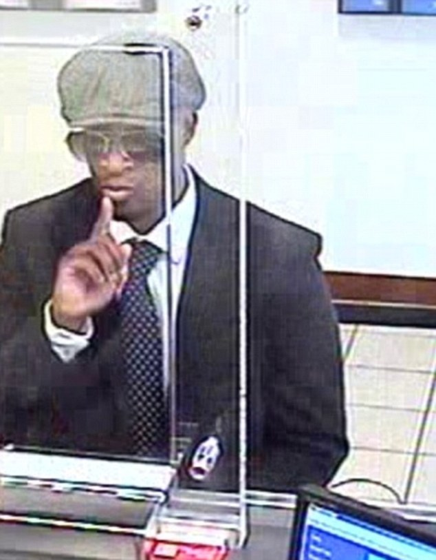 Police hunt bank robber caught on camera putting his