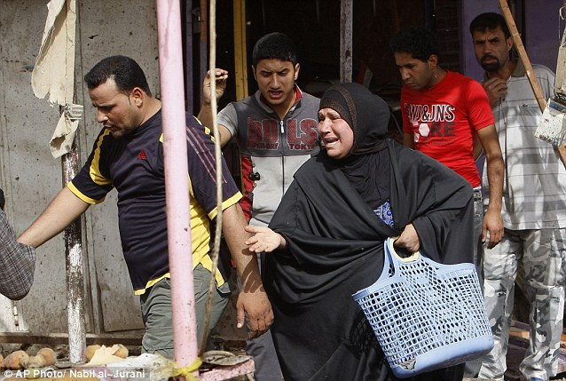 Terror: A shocked woman is left in tears as civilians peer at the destruction left by the bomb attack in Basra