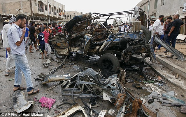 Aftermath: Civilians gather at the scene of another car bomb attack in Kamaliyah, a predominantly Shiite area of eastern Baghdad