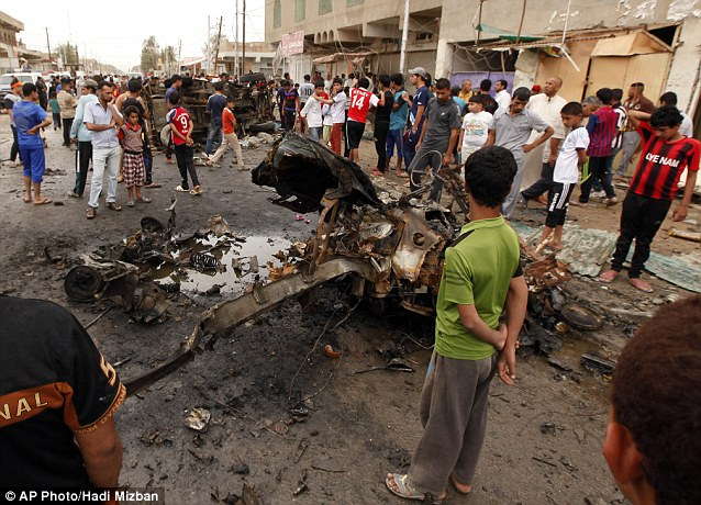Force: A boy looks at the shattered remains of a vehicle caught in the Baghdad bomb attack. The force of the explosion destroyed most of the vehicle