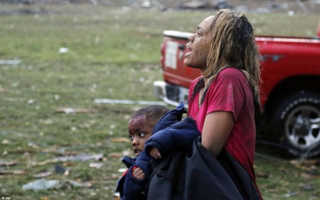 A woman carries an injured child to a triage center near the Plaza Towers Elementary School