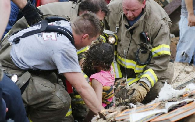 Desperate: A young girl is pulled from beneath the wall by rescuers as they desperately search for more survivors