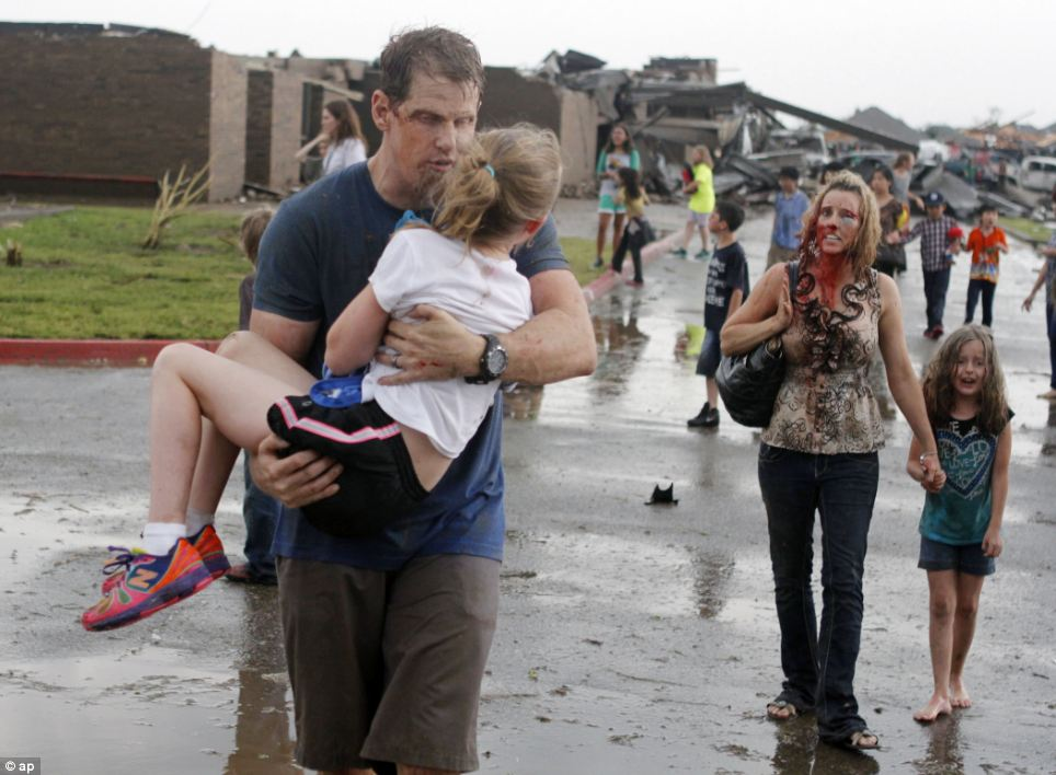 Horror: Teachers carry children away from Briarwood Elementary school after a tornado destroyed the school in south Oklahoma City