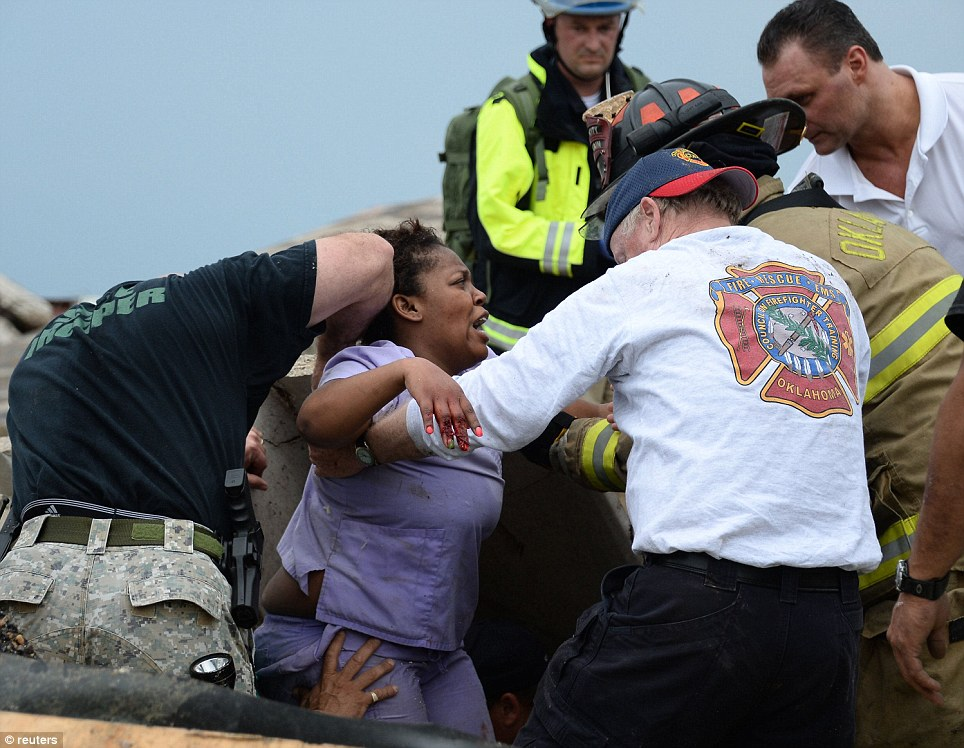 Rescue workers help free one of the 15 people that were trap at a medical building at the Moore hospital complex after a tornado tore through the area
