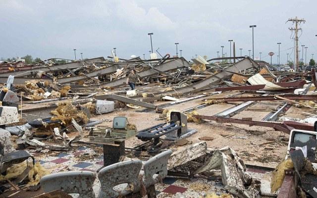 A woman walks through debris after a huge tornado struck Moore, Oklahoma, near Oklahoma City, May 20, 2013