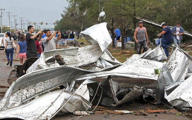 Twisted metal lies in the road as people take pictures of damage after a huge tornado struck on Monday