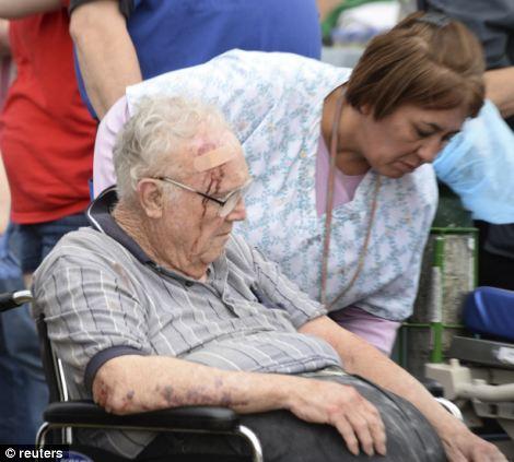 A nurse helps a older man that suffered a head injury
