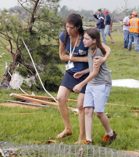 A parent rushes to embrace her child as a teacher escorts her away from Briarwood Elementary school