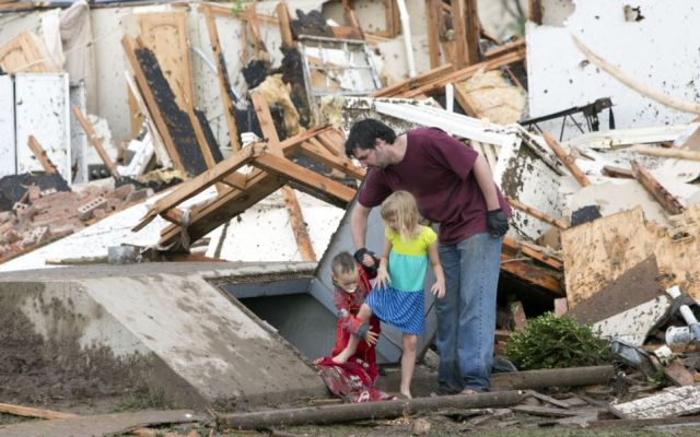 Lucky ones: A young family comes out of underground bunker after the tornado to scenes of devastation