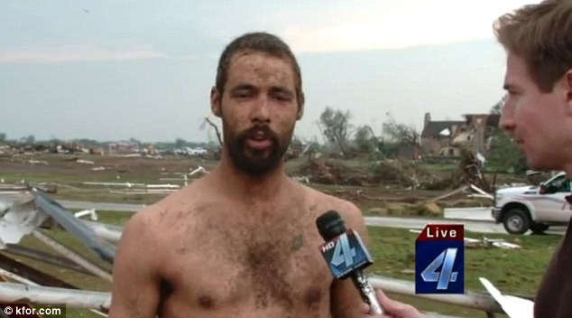 Lando Hite standing in front of the devastated farm where he lived