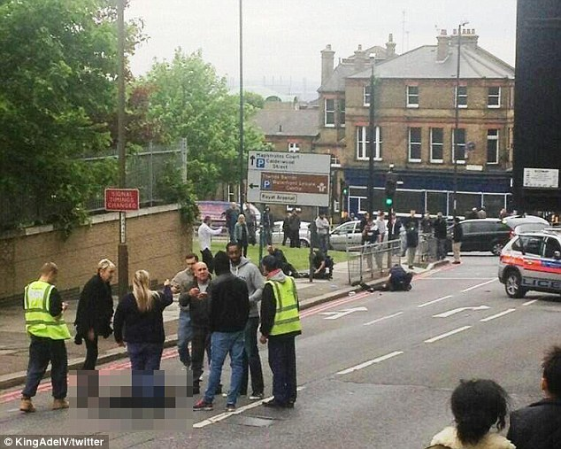 Horror: The scene in John Wilson Street, Woolwich moments after police arrived. The two attackers lie on the ground seriously injured after being attacked by police, while the soldier lies dead