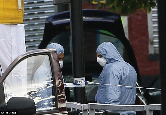 Probe: Police forensics officers investigate a car at a crime scene where one man was killed in Woolwich