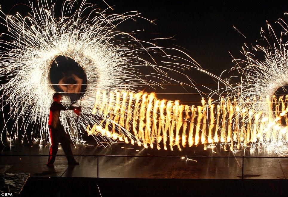 Создание знака: Этот огонь исполнителя загорелся вращающийся туннель пламени как два коллеги-художники выполняют в фоновом режиме