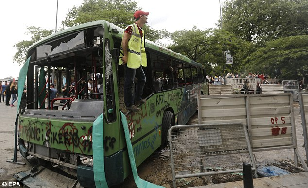 Damaged: An activist stands on a public bus that was damaged during the heavy clashes between protesters against the conservative government of Prime Minister Recep Tayyip Erdogan on Saturday