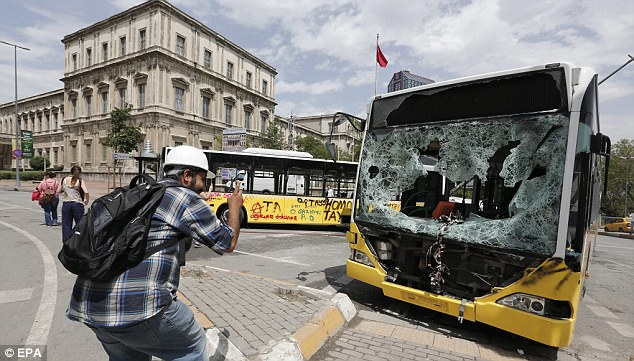 Target: An activist takes pictures of a public bus that was damaged during the heavy clashes between protesters against the conservative government of Prime Minister Recep Tayyip Erdogan on Saturday night