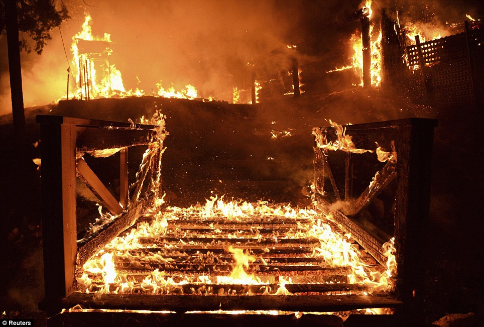 No way out: A wooden bridge erupted in flames near Lakes Hughes, California, as five homes were burned to the ground