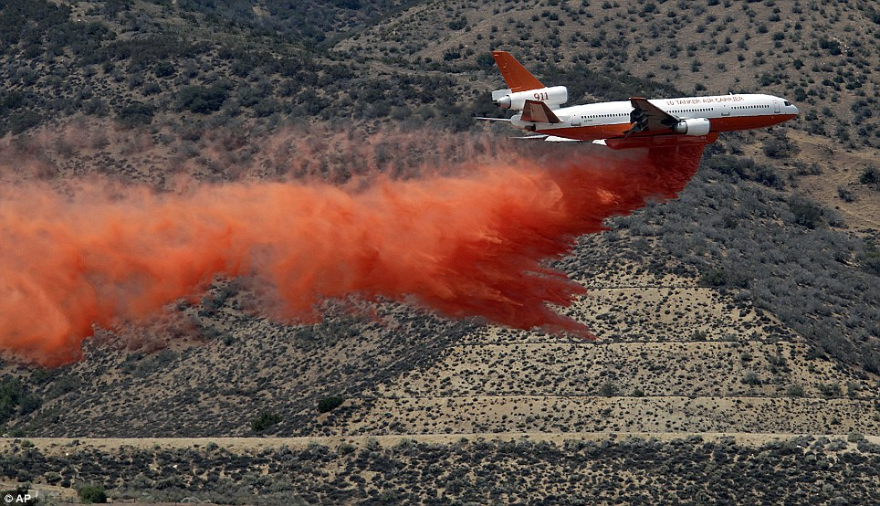 Fighting back: A DC-10 a aerial tanker drops fire retardant in the Angeles National Forest in an attempt to slow the spread of the 20,000-acre blaze