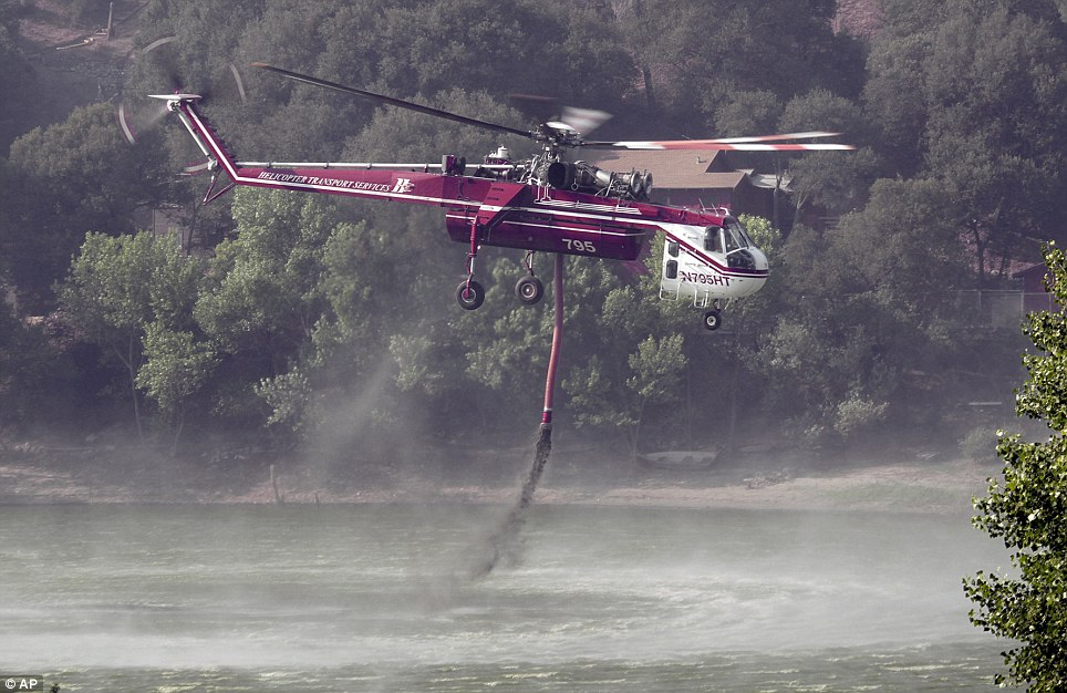Dousing the blaze: A helicopter sucks water from Lake Hues that it will then spray on the blaze that threatens 1,000 homes