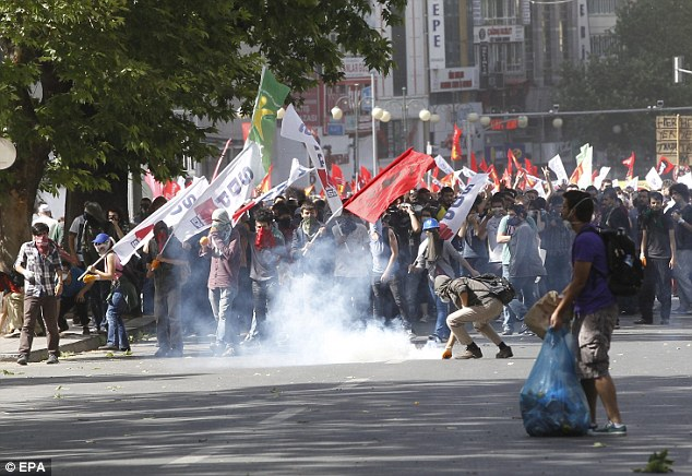 Escalating violence: A protester picks up a tear gas grenade to throw it back at riot police in Istanbul on Sunday