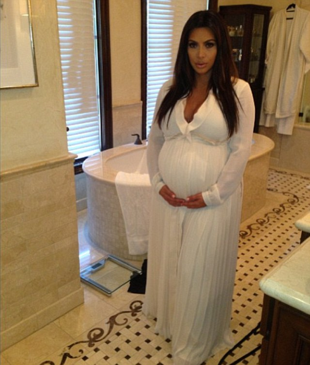 Not long to go: Kim Kardashian shows off her bump in a floor-length white dress in a Twitter picture, as her divorce is granted from Kris Humphries