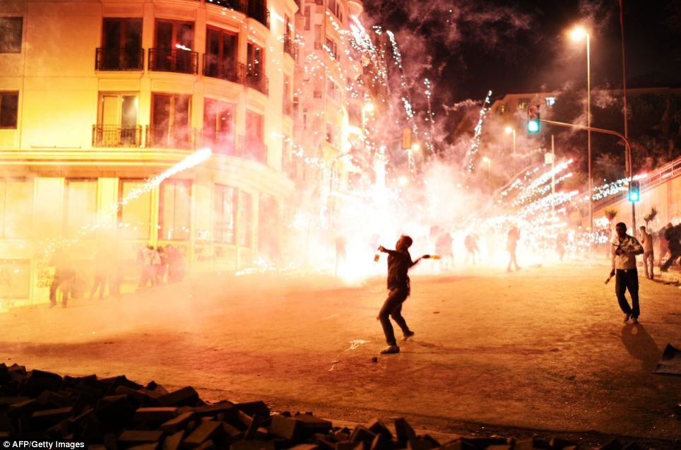 Dangerous: A demonstrator goes to throw a bottle as fireworks go off behind him