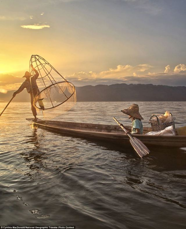 Photo and caption by Cynthia MacDonald. A father and daughter with a fish in the net at sunset on Inle Lake, Myanmar. Location: Inle Lake, Myanmar