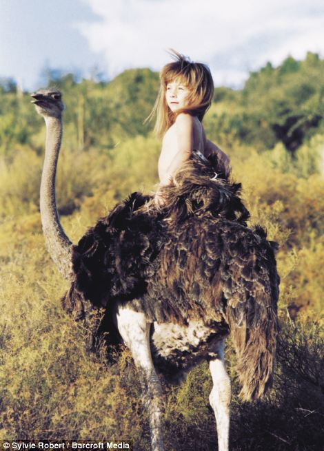 Tippi aged 6 sitting on the back of Linda, a tamed ostrich in South Africa