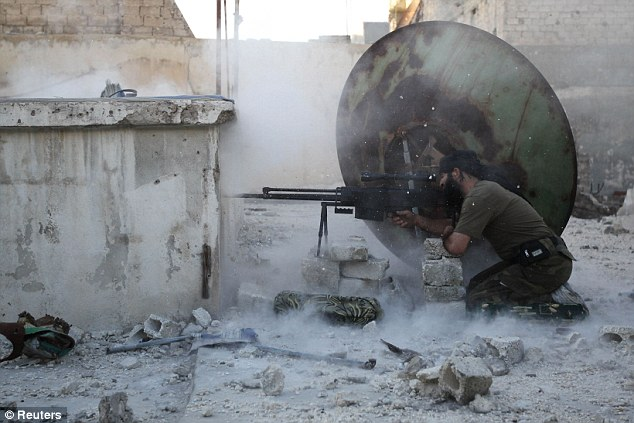 A member of the Free Syrian Army shoots back at a sniper in Aleppo, where a 15-year-old boy was killed by Al Qaeda-linked insurgents for apparently saying he did not believe in the Prophet Mohammad