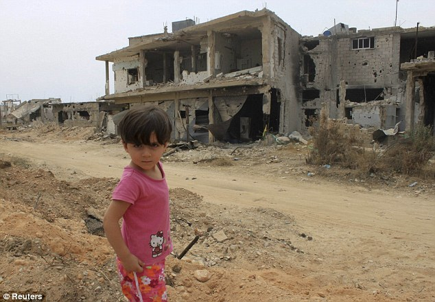 A child is seen in front of a damaged house in Qusair after fierce fighting over the past week
