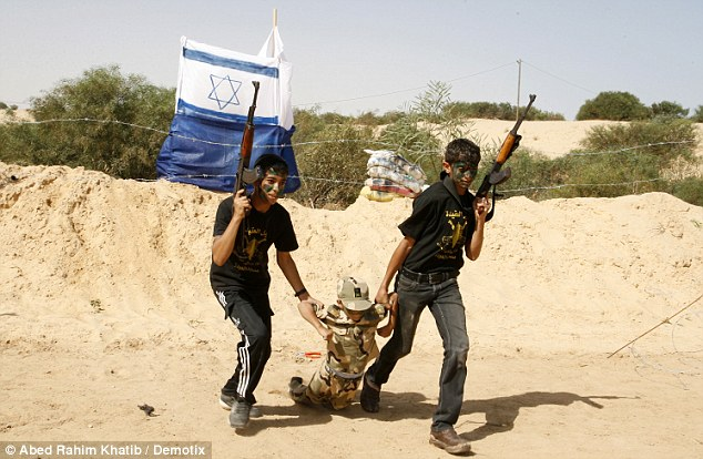 Dummy run: Two children practise kidnapping an 'Israeli soldier' in the desert sun