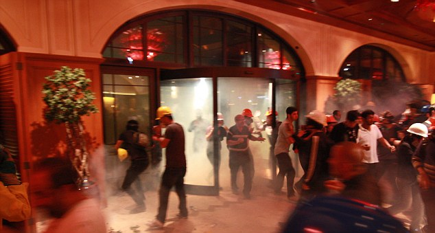 Fleeing: Hotel guests and protesters escape the fumes of the tear gas thrown into the lobby of the Divan Hotel during the police operation