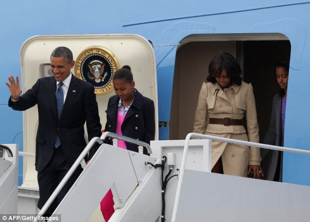 Touch down: US President Barack Obama arrived in Belfast along with his two daughters and wife Michelle who looked stylish in a Burberry coat