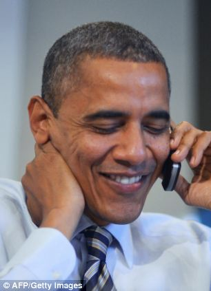 US President Barack Obama calls a volunteer as he visits a campaign office in Chicago, Illinois, on election day, November 6, 2012