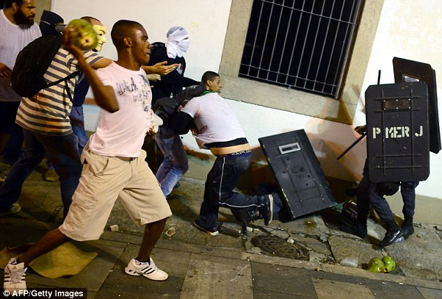 Trouble: Police struggle to contain the demonstrators, with one appearing to throw a coconut at officers