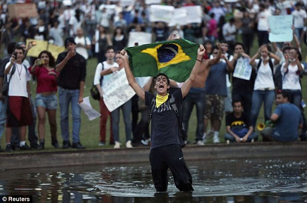 Anger: A demonstrator with the national flag protests against the soccer Confederation's Cup and the government of Brazil's President Dilma Rousseff in Brasilia