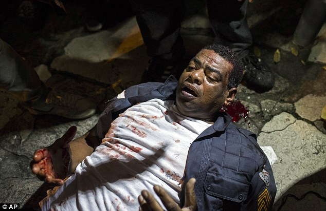 Hurt: A policeman lies injured on the ground after clashing with demonstrators