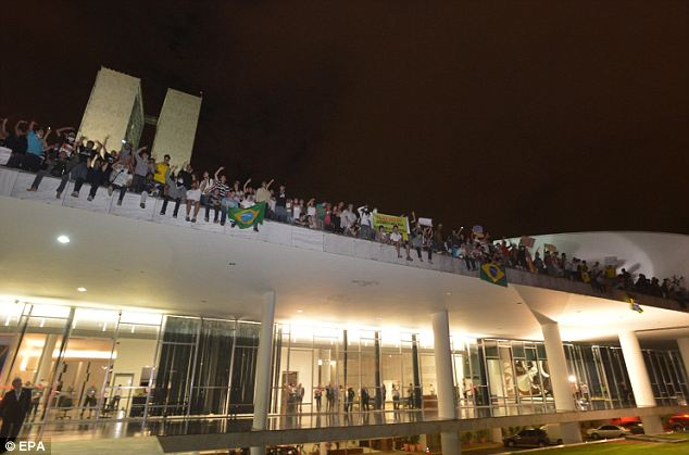 Peaceful: Hundreds of people protest on the roof of the national congress against rising public transport costs in Brasilia