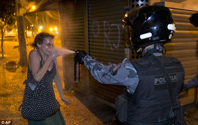 Crowd control: A military police peper sprays a protester during a demonstration in Rio de Janeiro on Monday, June 17