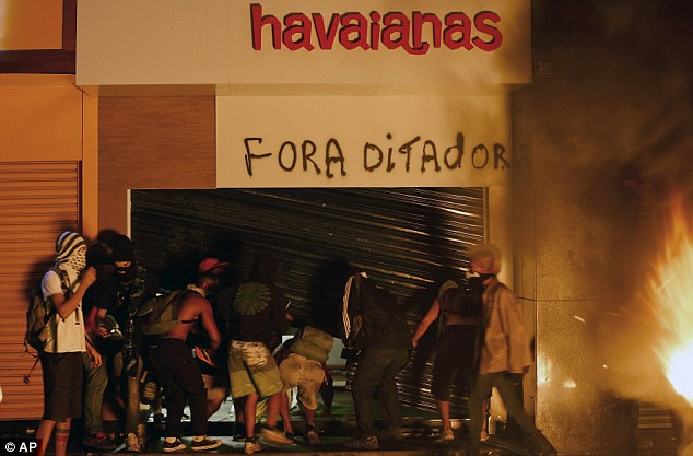 Vandalism: Protesters break into a sandals' store as the protests begin to escalate
