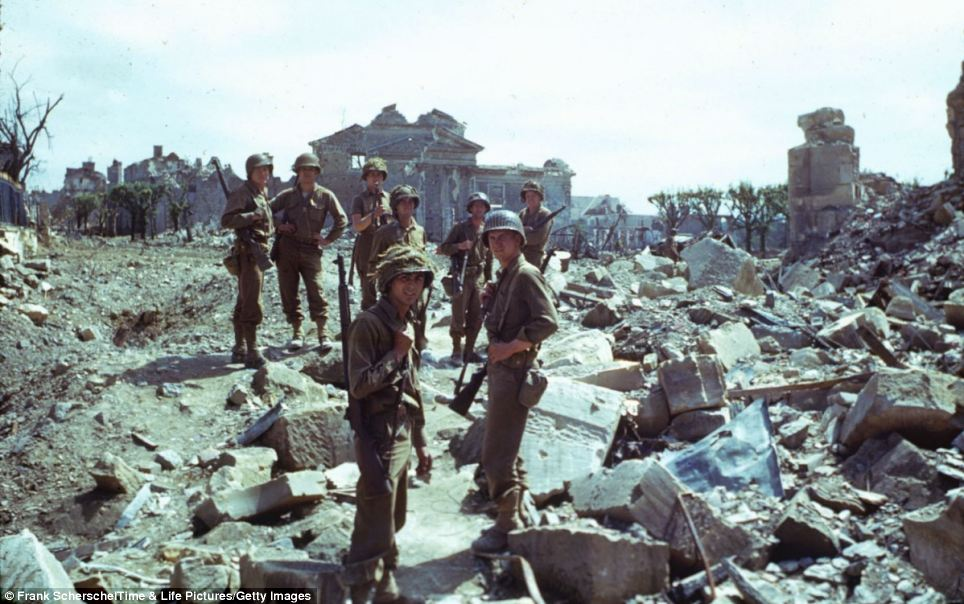 American troops pose for a photograph amongst the ruins of northern France in the summer of 1944