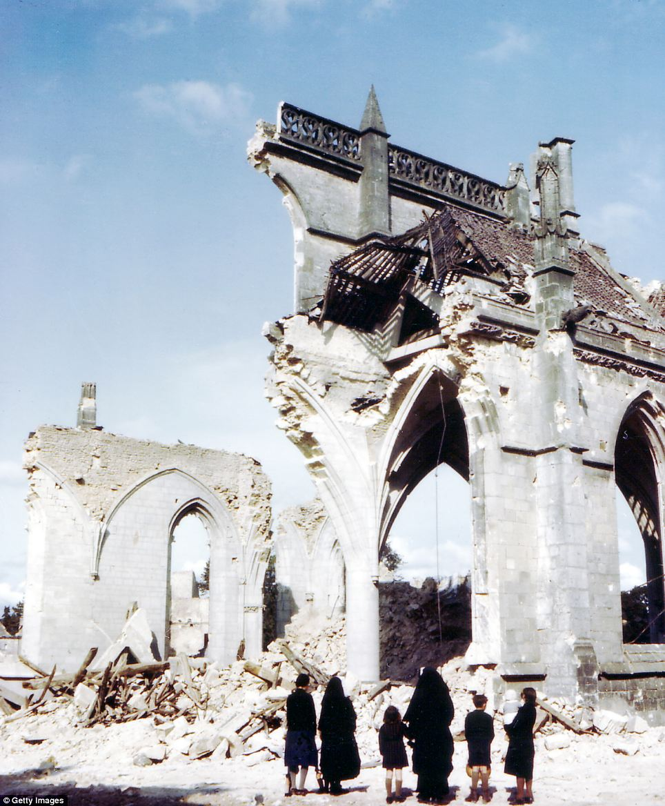 Some nuns and some children look on at the ruins of almost totally destroyed church