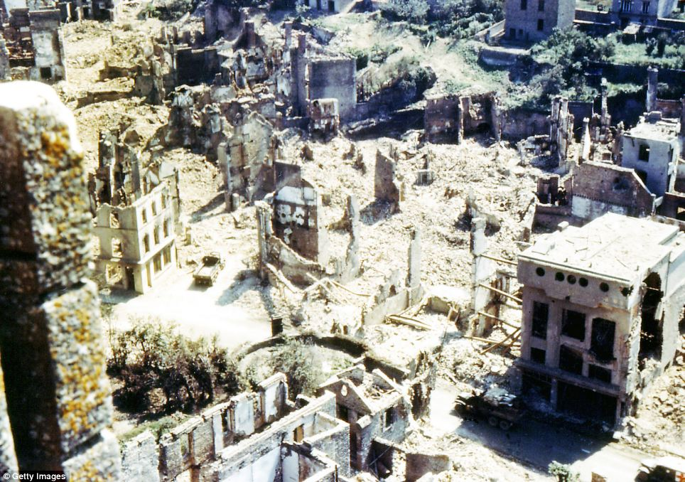 An American ambulance, a jeep and a truck are driving through the ruins of Saint-Lo, which was almost totally destroyed by 2,000 Allied bombers when they attacked German troops stationed there