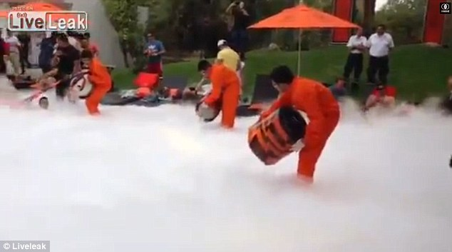 Bad move: Employees dressed in orange unfirms could be seen pouring liquid nitrogen into the pool, which quickly filled with thick white smoke
